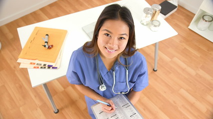 Portrait of female Asian doctor smiling and writing