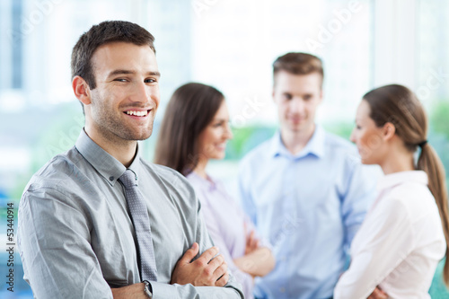Businessman with coworkers in background