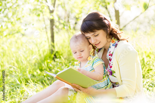 happy mother reading a book to baby in garden