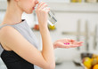 Closeup on young housewife eating pills and drinking water