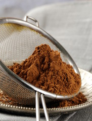 cocoa powder in a metal sieve on gray background
