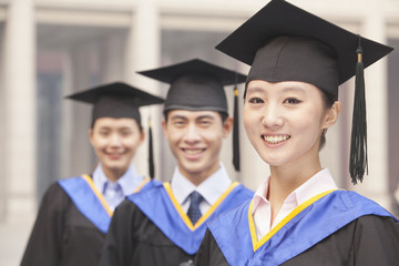 Three University Graduates Smiling in a Row