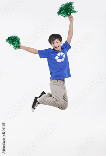 Young man with recycling t-shirt cheering with pompoms, studio shot