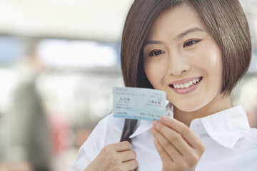 Young Woman Looking at a Train Ticket