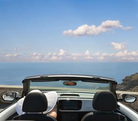 Woman in white hat in an open car