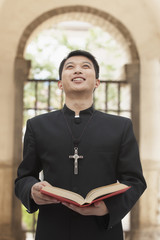 Young Priest Looking to Sky in Front of Doorway