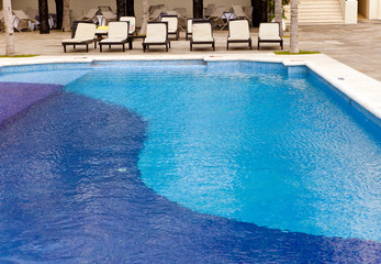 Empty chaise lounges near  pool