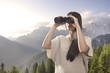 Young woman watching with binocular