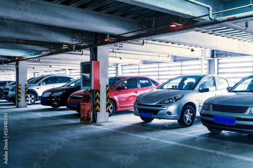 Leinwanddruck Bild Parking garage, interior with a few parked cars.