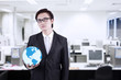 Businessman hold world globe at office