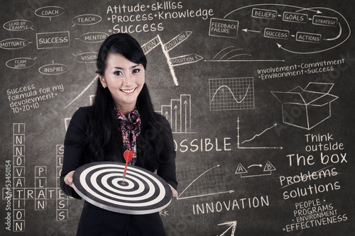 Businesswoman hold bull's eye in class
