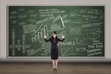 Businesswoman thumbs up on written chalkboard background