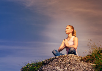 Young concentrated female meditating on hill at the sunset