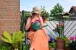 Frau mit Gießkanne auf dem Balkon