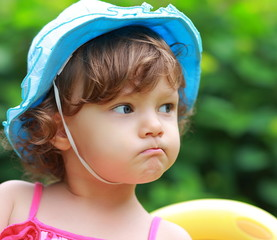 Angry baby girl looking in blue hat on summer background. Closeu