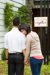 disappointed asian couple in front of a house