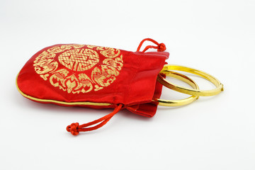 golden bracelets and red bag