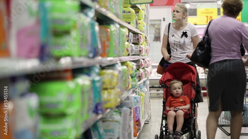 Mother with her boy in baby carriage in the supermarket