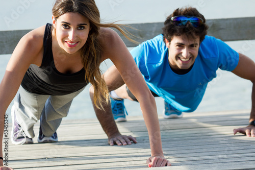 Couple doing push ups near the sea