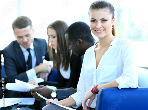 Successful business woman sitting with her staff in background