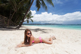 Young beautiful woman lying on the sand at the beach