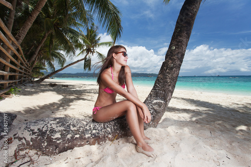 Young beautiful woman sitting on the palm tree