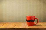 Red cup with paper mustache on wooden table