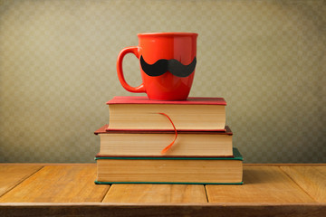 Vintage books and cup with mustache on wooden table
