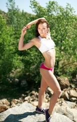 Slim athlete girl in nature, posing on the rocks
