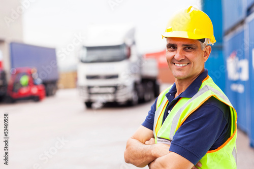 senior shipping company worker standing outside warehouse