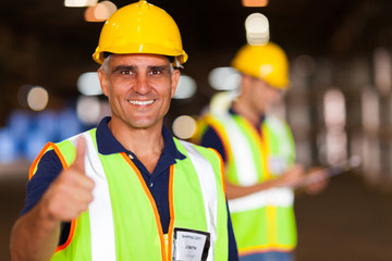 senior shipping company worker giving thumb up