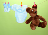 Baby clothes hanging on clothesline, on green background