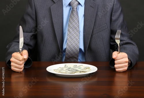 Young businessman having dinner dollars on black background