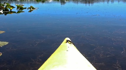 Close up bow of yellow kayak moving forward in blue lake waters