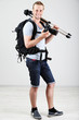 Handsome photographer with camera and tripod, on gray