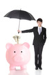 Business Man holding umbrella protect your money