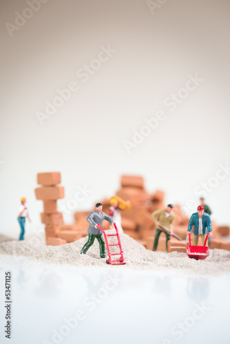 Miniature men doing brickwork with overcast sky like background