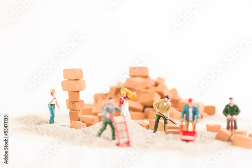 A team of miniature workmen doing construction work