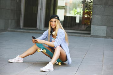 Young woman sitting on the skater and subject a smartphone