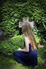 Junge Frau vor dem Grab