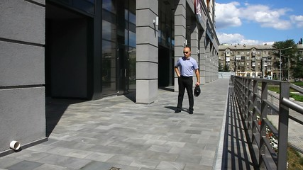 Businessman answers a cell phone call near an office center