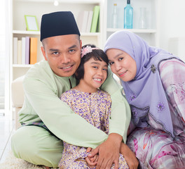 Muslim parents hugging child