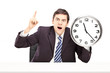 Angry businessman holding a clock