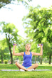 Female in a park sitting and exercising with dumbbells