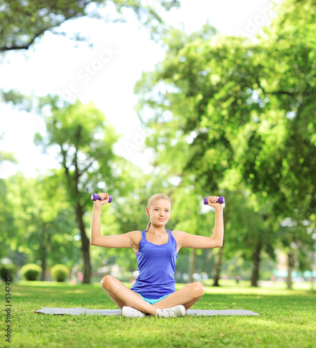 Female in a park sitting on a mat and exercising with dumbbells