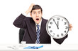 Surprised man sitting in an office and holding a clock