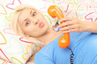 Young blond woman lying in bed with a telephone in hand and blow