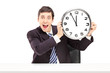 Young happy businessman holding a clock
