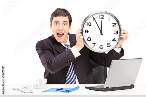 Young happy businessman in an office and holding a clock