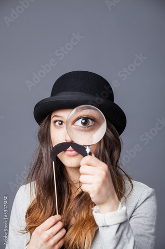 Pretty girl with hat, paper mustache and magnifying glass